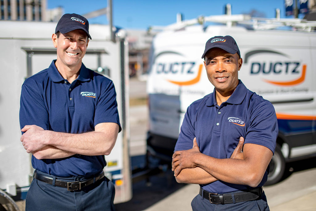 DUCTZ air duct cleaning franchise technicians in front of vans